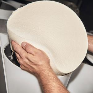 Fromager à l'oeuvre dans la manipulation d'une meule de fromage